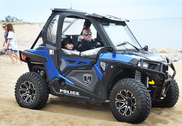 BRYAN EATON/Staff Photo. Ryan Mancia, 8, gets a ride in a Newbury Police Department ATV driven by officer John Baker on Tuesday afternoon after having a pizza lunch with Chief Michael Reilly, Baker, officer Mark Smigielski and his fellow third-grader and best friend Dalton Giusti.