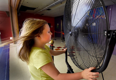 BRYAN EATON/Staff Photo. Niveah Currier, 7, cools down in front of one of the fans blowing the air around in the game room of the Boys and Girls Club in Salisbury as the air was still a little muggier inside than out. The air is forecast to be even drier today and the weather great for the weekend.