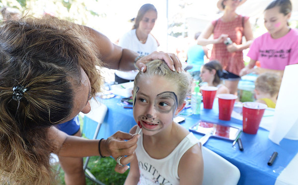 BRYAN EATON/Staff Photo. Lillyanne Sachetti, 8, of South Hampton, N.H. whose mom, Kristyn is from Newburyport, gets a puppy facepaiting by Tracey Zimirowski for Georgetown High School cheerleaders fundraiser.