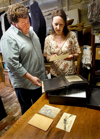 BRYAN EATON/Staff Photo. Kevin MacDonald of the Custom House Maritime Museum looks through a diary and old photos, of Arthur W. Woods, Lighthouse Keeper of Plum Island Light from 1905 until his death in 1919, with his descendant Jenn Bogard. She and her family are donating the items to the museum.
