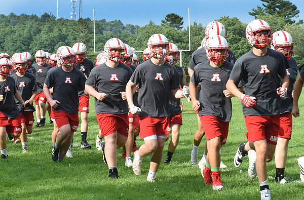 BRYAN EATON/Staff photo. Amesbury High School football team warms up with laps around the field.