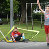BRYAN EATON/Staff Photo. Ethan Koucznik, 11, goes down with the net trying to make a save, though he wasn't the goalie, in a game of street hockey at the Amesbury Town Park. Amesbury Youth Recreation was holding the camp this week, with Thursday being American Theme and Moustache Day.