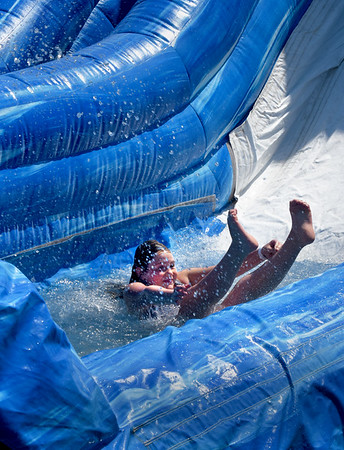 BRYAN EATON/Staff Photo. Elizabeth Carty, 11, of Seabrook makes a splash at the bottom of the waterslide at the Boys and Girls Club at the end of the week. The summer program ends on August 30 and is the club is closed the following week before reopening for afterschool programs.
