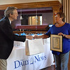 BRYAN EATON/Staff Photo. Daily News Editor Richard K. Lodge hands a gift bag to Inn Street Barber owner Esther Sayer.