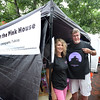 "Bryan Eaton/Staff photo. Rochelle Joseph, left, and Eric Hoover and their group trying to save ""the pink house"" on Plum Island Turnpike from demolition have a booth on Inn Street selling various items, including t-shirts to raise funds."