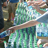 JIM VAIKNORAS/Staff photo Volunteers from Walgreens hand out water at the Yankee Homecoming road race course Tuesday.