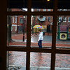 JIM VAIKNORAS/Staff photo A woman walking in the rain on Inn Street in Newburyport is framed in the doorway of the Purple Onion Saturday afternoon