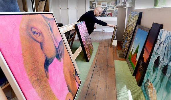 BRYAN EATON/Staff Photo. Kaveh Mojtabai looks through the entrants at the Newburyport Art Association.