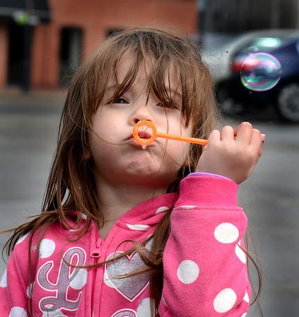 JIM VAIKNORAS/Staff photo  Kianna Wilson 3, of Newburyport blows bubbles Monday morning on Water Street in Newburyport.