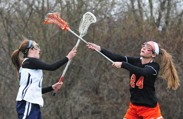 BRYAN EATON/Staff Photo. Triton's Kaitlyn Muldowney, left, throws past a Woburn defender.