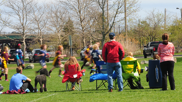 JIM VAIKNORAS/Staff photo Spectators watch as soccer player at Cashman Park in Newburyport sprint by on a sunny Saturday afternoon.