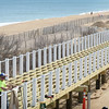 BRYAN EATON/Staff photo. People who went to Salisbury Beach on Monday walk by the boardwalk being constructed on Ocean Front South. The boardwalk should be completed in time for the summer season
