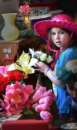 BRYAN EATON/Staff photo. Students in Amiee Farrell's kindergarten class spread some color on a gloomy Thursday morning with Flower Day. Zoey Owen, 6, pictured, and her classmates put together bouquets of artificial flowers and brought them around to different spots in the school as the main office and nurses office.