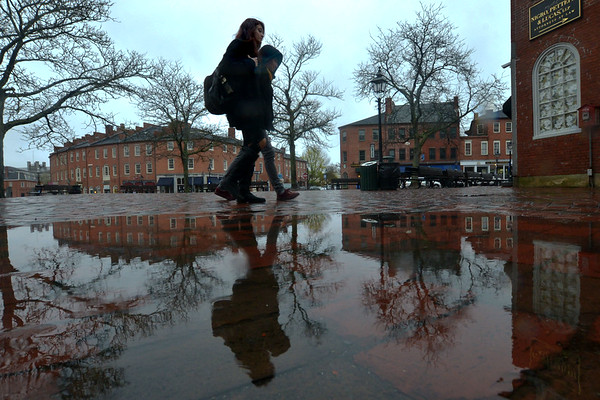 JIM VAIKNORAS/Staff photo Veronica Lavia and Vincent Aquilar, both of Plum Island, are reflected in a puddle as they walk in the rain through Market Square in Newburyport Friday morning.