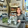 JIM SULLIVAN/Staff photo. Eighteen Friend Street owner Coleen Magowan holds some Amesbury photography.