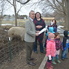 JIM VAIKNORAS photo Representative Lenny Mirra presents at citation Friday to Bethany Groff Dorau, region manager at the Spencer-Peirce-Little Farm in Newbury, on behalf of Big Dave, a beloved pig who passed away earlier this month. Joining them were teachers and kids from the Farm Friends program and the newest resident at the farm Sky the goat.