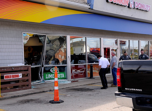 JIM VAIKNORAS photo Emergency response personal look over the scene of an accident, an car into a building at the Sunoco One Stop on Rt 1 in Seabrook Monday morning.