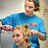 "BRYAN EATON/Staff photo. Emily Tucker, 17, seated who plays Violet Gold, gets her hair styled by Cecilia Shelter, 17, who plays Alice Tierney in ""Hello My Baby."""