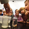 BRYAN EATON/Staff photo. Students watch as Amy LeBlanc drops a small carrot into salted water which makes it more buoyant than the carrot that sank to the bottom in plain water in the jar at right. They were doing different science experiments in the STEM lab at one of the Bresnahan School's Afterschool Programs.
