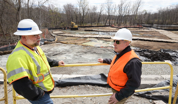BRYAN EATON/Staff photo. National Grid project manager Kenneth Lento, left, and Thomas Barrasso, director of Energy and Environmental Affairs for Amesbury check out the site remediation on the Powow River which is almost complete.