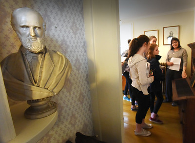 BRYAN EATON/Staff photo. The people who run the John Greenleaf Whittier Home in Amesbury invited students from the River Valley Charter School to visit the site and learn about the famous poet. They had followed the students' attempt to the get the second span of the Whittier Bridge on Interstate 95 named after William Lloyd Garrison, a contemporary and friend of Whittier. Here, Nan Becker, show students Whittier's desk.