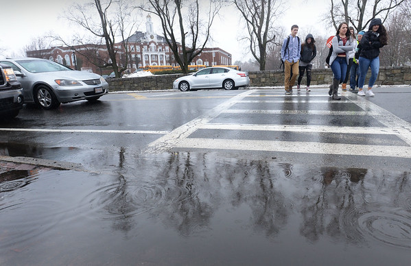 BRYAN EATON/Staff photo. Newburyport High School students cross High Street after classes Tuesday reflected in a puddle. Rain returns Thursday with the weekend looking to be sunny and warm.