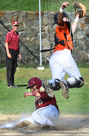 BRYAN EATON/Staff photo. Newburyport's Jayden Medeiros slides into home as Ipwich catcher Shawn Grady reaches for the ball.