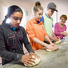 BRYAN EATON/Staff photo. Art teacher Joan Gessner sprinkles flour on a work counter as her students knead some dough in her Amesbury kitchen; from left Debanshi Jain, 11, Kristin Litzenberg, 13, and Jack Vachon, 15, with Tara Duggan and Renee Vachon, both 13, out of view. Since it was school vacation this week and her students had extra time, they made the dough, and while it was proofing, then baking, worked on their art projects.
