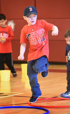 BRYAN EATON/Staff photo. Seth Greenwood, 6, goes through an obstacle course at the Bresnahan School wearing a Red Sox shirt and hat. It was Spirit Day at the Newburyport school for the home opener and students are collecting coins for the Jimmy Fund all week.