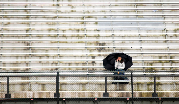 JIM VAIKNORAS/Staff photo Karen Pons huddles under an umbella during the Newburyport girls lacrosse team plays Bishop Fenwick Saturday in the rain at World War Memorial Stadium in Newburyport. Pons daughter Maggie plays for the Clipper who won the game 16-6.