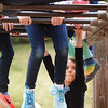 BRYAN EATON/Staff photo. Destiny Grace, 8, maneuvers around the hanging legs of her friends on a monkey bar during recess at the Amesbury Elementary School on Monday. Recess is likely to be held indoors Tuesday and Wednesday with rain in the forecast with nice weather returning for the weekend.