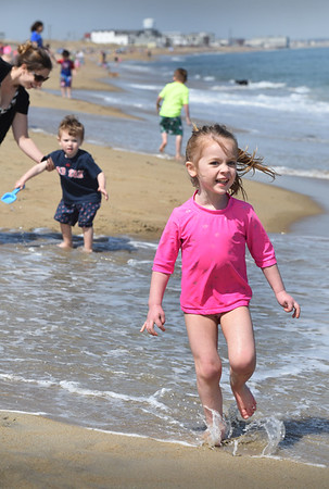 BRYAN EATON/Staff photo. Juliet Perry, 4, of Newburyport hit the sands of Salisbury Beach along with her brother, Austin, 2, and mother Kelly, rear, left. There were scores of people joinging them with the temperature over the 80-degree mark.