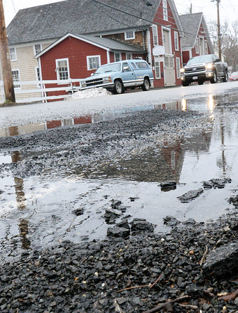 BRYAN EATON/Staff photo. Potholes have been spotted throughout the area and crews have been seen filling them. Here on Main Street in Amesbury, at Lowell's Boat Shop, some are still a nuisance and the rain creates puddles hiding the holes from motorists.