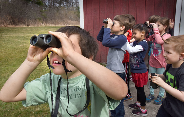 BRYAN EATON/Staff photo. Jake Carpenter, 7, left, and classmates look for birds, squirrels and other creatures in the woods behind Amesbury Elementary School. The students in Bruce McBrien's technology class are used to learning on computers, but Thursday morning he handed them binoculars he procured with a grant for them to learn about optics, another kind of technology, to see things close up and far away and to make comparisons.