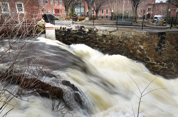 BRYAN EATON/Staff photo. Melting snow and heavy rains of late make for a rushing Powow River in Amesbury's Upper Millyard. More rain is expected late Thursday which will increase water flow even further.
