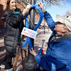 BRYAN EATON/Staff photo. Several members of the Exchange Club of Greater Newburyport put up around 50 blue ribbons around downtown Newburyport Friday morning to be displayed for two weeks to mark Child Abuse Prevention Awareness Month. Putting one up in Market Square are Barbara Griffith with Mike Viccaro with Anthony Marks, 7, helping out handing ties to them.