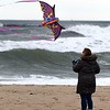 JIM VAIKNORAS/Staff photo Julie Winslow of Chelmsford takes advantage of the high winds Tuesday to fly a dragon kite at Salisbury Beach Reservation.