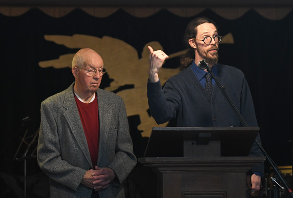 JIM VAIKNORAS/Staff photo Duncan MacBurnie and Rev. Matt Willis-Goode speak at the dedication of the Angel Gabriel weather vain at the People Methodist Church in Newburyport. The event was held inside due to the cold weather.