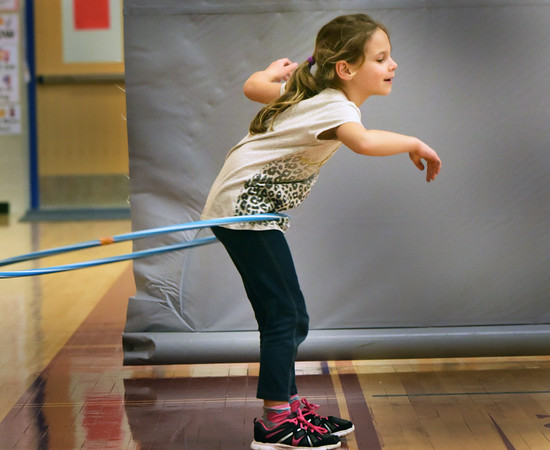 "BRYAN EATON/Staff photo. Kiana Durbin, 7, does her best to keep a hula hoop from dropping to the ground in the gymnasium at the Bresnahan School in Newburyport on Wednesday. She was in the afterschool program ""Cardio and Go"" taught by Jane Greenblott where younsters excercise, do some competitive sports and games."
