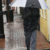 CARL RUSSO/staff photo. Chris Poulack walks down State Street Monday afternoon. Heavy rain plagued the Newburyport area on Patriots' Day. 4/16/2018