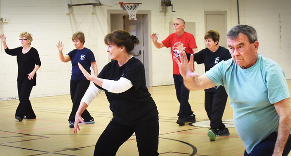 BRYAN EATON/Staff photo. Barbara Tindall's Tai Chi students move down the gymnasium at the Brown School in Newburyport, from left, Susan Gaylord, Lynn Mather, Allyson Lawless, Mike Mather, Jean Abel and Don Cornoni. World Tai Chi day is on Saturday, and the Daoist Benevolent Association will be one of three tai chi classes joining together for a morning of workshops, demonstrations and activities in Waterfront Park.