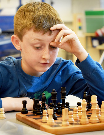 BRYAN EATON/Staff photo. Tyler Bergeron, 8, works on his next move in a chess game at the afterschool programs at the Bresnahan Elementary School in Newburyport on Monday afternoon. He was playing with instructor Lukas Woodger of Newburyport who is in the high school level at the Clark School in Rowley. It's the fifth week of class and he said some of the attendees had a basic understanding of the game when they started and have been working to improve.