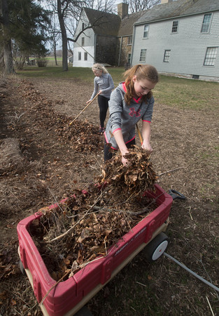 JIM VAIKNORAS/Staff photo Vivian Gijsbers, 11, and Emerson McCormick, 11, clean out a flower bed at the Spencer Pierce Little Farm in Newbury Friday morning. The girls were part of a group of about 50 students from grades 4, 5, and 6 from the River Valley Charter School in Newburyport who came out to the farm on Community Service Day.