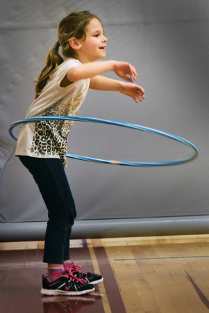 """BRYAN EATON/Staff photo. Kiana Durbin, 7, does her best to keep a hula hoop from dropping to the ground in the gymnasium at the Bresnahan School in Newburyport on Wednesday. She was in the afterschool program """"Cardio and Go"""" taught by Jane Greenblott where younsters excercise, do some competitive sports and games."""