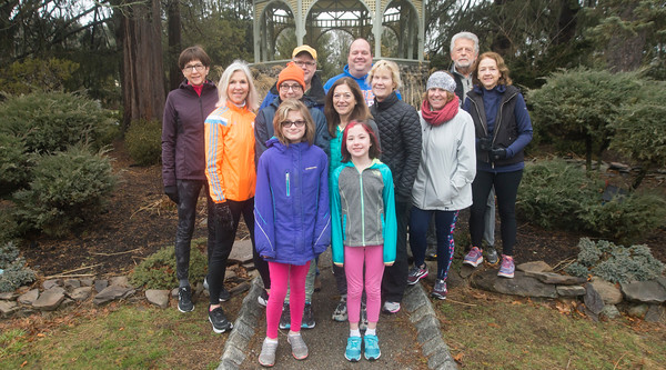 JIM VAIKNORAS/staff photo Nancy McCarthy, in orange jacket, with her running class at Atkinson Common in Newburyport.