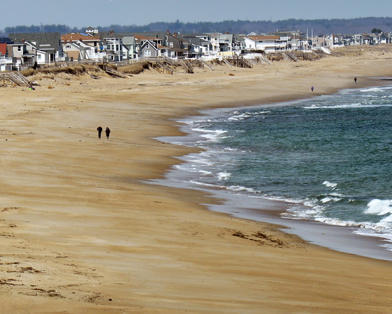 BRYAN EATON/Staff photo. A couple hardy types took a stroll on Salisbury Beach, though it was sunny, it was cool with and southeast wind. It warms up for Friday and Saturday but the cold returns on Sunday.