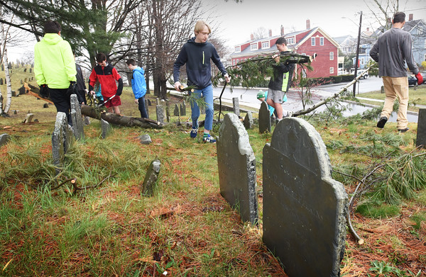 BRYAN EATON/Staff photo. Nock Middle School students clear fallen branches at Old Hill Burying Ground in Newburyport on Thursday morning. They are travelling today to Crow Lane Landfill to see the recyling operation as they are being exposed to volunteering in the community and sustainability.