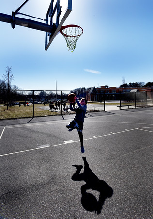 "BRYAN EATON/Staff photo. Nate O'Donnell, 10, lays up a shot during YWCA afterschool activities at the Bresnahan School on Monday afternoon. He's a fan of Boston sports in general but says he ""loves the Celtics."""
