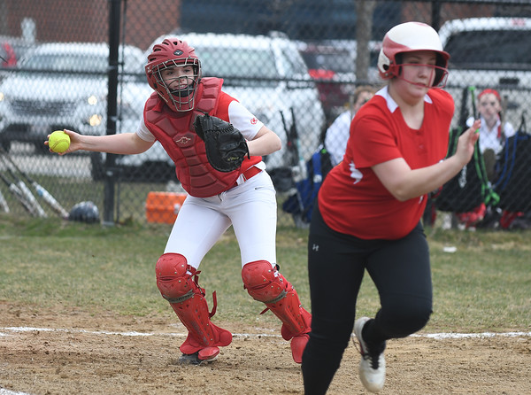 JIM VAIKNORAS/Staff photo  Mascomonet catcher Eliza Reimold throws out an Amesbury runner at Amesbury Middle School Friday.