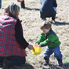 JIM VAIKNORAS/Staff photo Lucia Boyton, 1, gathers all his eggs in one basket with the help of his mom Rachel during an egg hunt at the Bradstreet Farm in Rowley. The event venue which recently opened, brought back the egg hunt which for years was put on by the Bradstreet family.